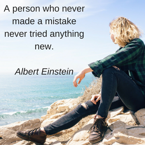 """A woman sitting on the shore looking out into the ocean with quote from Albert Einstein: """"A person who never made a mistake never tried anything new."""""""