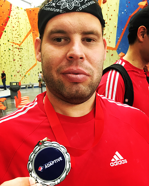 Shawn holding his medal at an adaptive rock-climbing competition