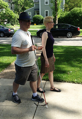 George and Polly Abbott using sighted guide while strolling their neighborhood
