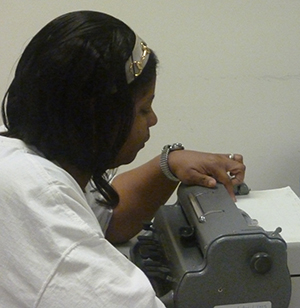 Loretta proofs her braille at the braillerwriter