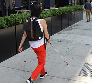 Andrea uses her cane to walk confidently down a busy Chicago sidewalk