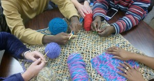 Four people at Knit and Crochet with their projects
