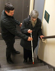 Alex helps Gina use her cane to navigate the stairs