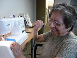 Victoria pumps her fist after using a sewing machine for the first time after losing her vision.