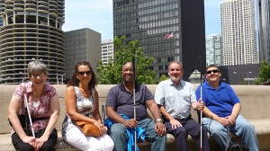 Gina, Stella, Aaron, Marv and Jose sitting on a bench overlooking the Chicago River