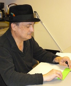 Tony learning to use his slate and stylus in braille class