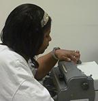 Loretta proofs her work at the braillewriter