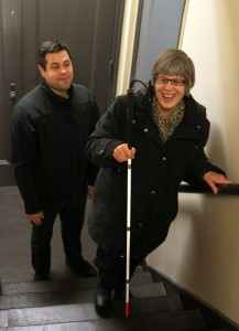 Alex, COMS, watches Gina use her cane to navigate the stairway.