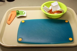 A light colored tray holds a dark colored cutting board, bowl with a variety of kitchen tools and a knife.