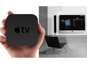 Hand holding Apple TV with television, speaker and chair in the background
