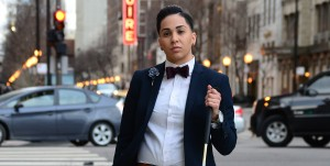 Madeline wearing her signature bow-tie, a blue blazer and grey pants proudly posing with her cane