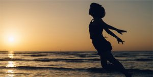 Silhoutte of a woman with arms outstretched at sunset