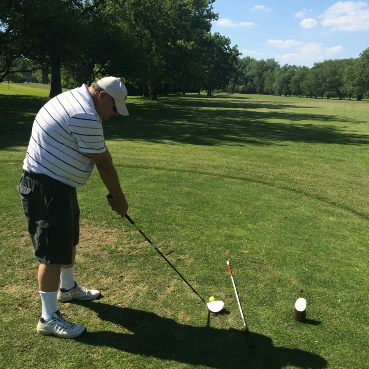 Chuck uses a golf club to line up his ball to the hole