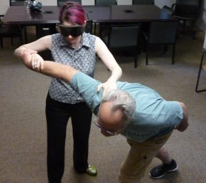 Polly, under blindfold, demonstrates her technique to the 1Touch instructor