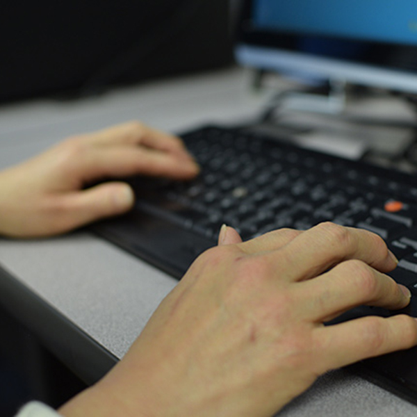 Two hands resting on a computer keyboard