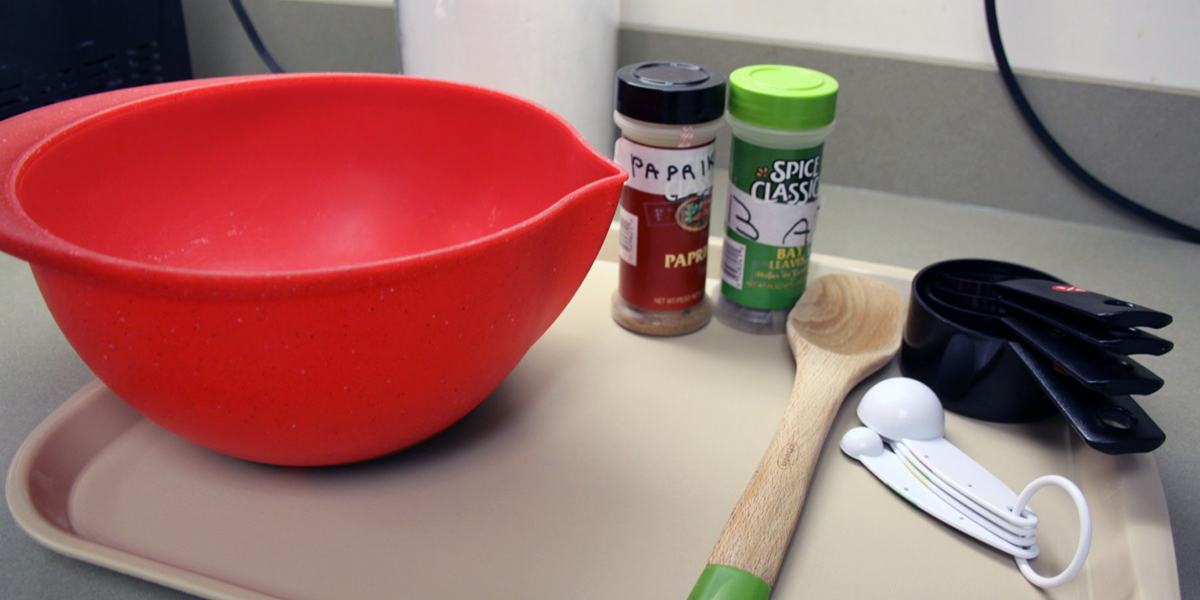 A mixing bowl, measuring spoons and seasonings on a tray
