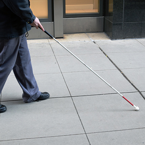 Man walking down the sidewalk with a cane.