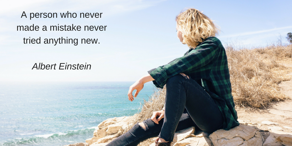"A woman sitting on the shore looking out into the ocean with a quote from Albert Einstein: ""A person who never made a mistake never tried anything new."""