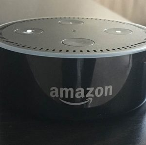 The Amazon dot, one of the Amazon Voice products, with a sleek design, about the size of a hockey puck