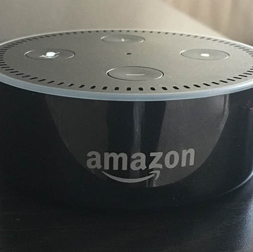 The Amazon dot with a sleek design, about the size of a hockey puck