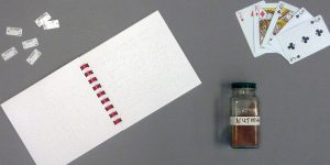 A braille calendar, braille clothing labels, braille playing cards and a jar of nutmeg with a large print and braille label