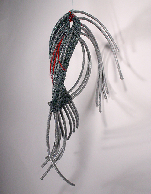 Grey sticks are bent in a circular sculpture encased in greay and red fiber.
