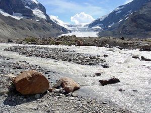 A group of rocks in the foreground lay at the bend of a frozen river winding toward the background between two snow-covered mountains.