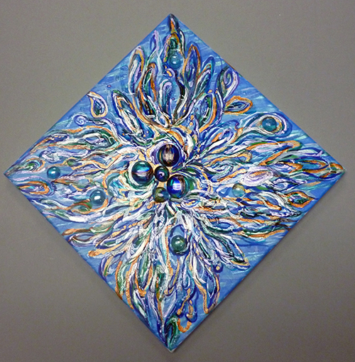 Strands of paint in various colors blossom from the center of the canvas to the edges with a group of glass beads in the center.