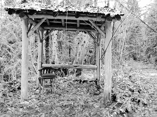 A black and white photo depicting a ramshackle wooden canopy protecting a single chair in the woods with leaves covering the ground.