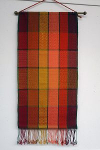 A scarf woven in a plaid patters of reds and yellows