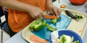 Client in Second Sense's cooking classes uses a knife to cut up a green pepper.