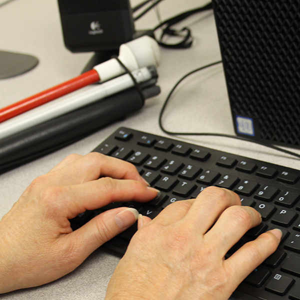 Hands on keyboard with folded white cane on desk.