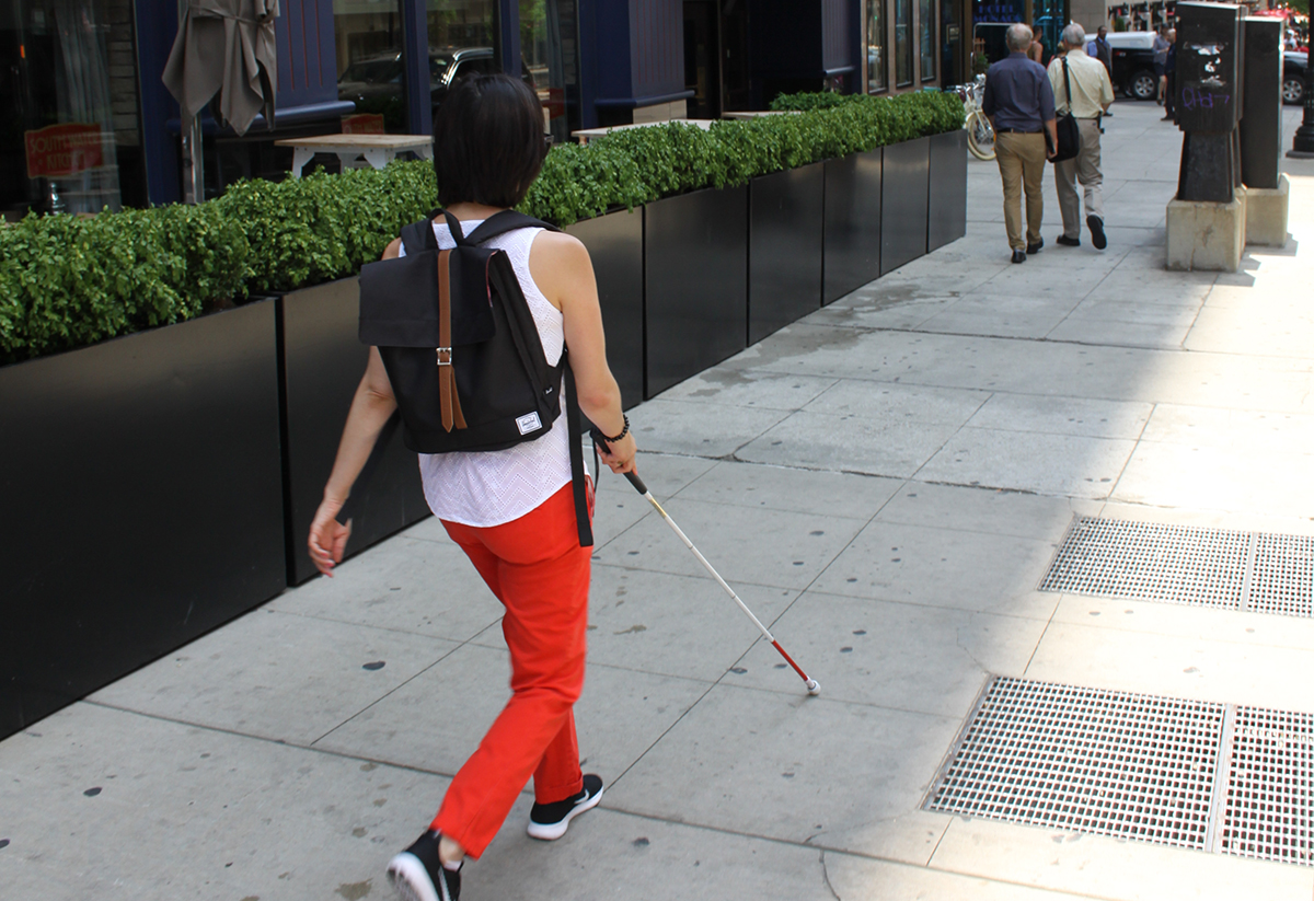 Andrea walking confidently down a city sidewalk using her white cane