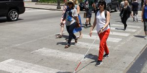 Andrea crossing a downtown intersection using her white cane