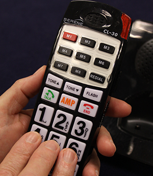 Three fingers poised on the middle line of numbers on the keypad of a wireless phone