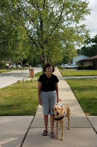 Kathy with Rowen in Harness on the sidewalk