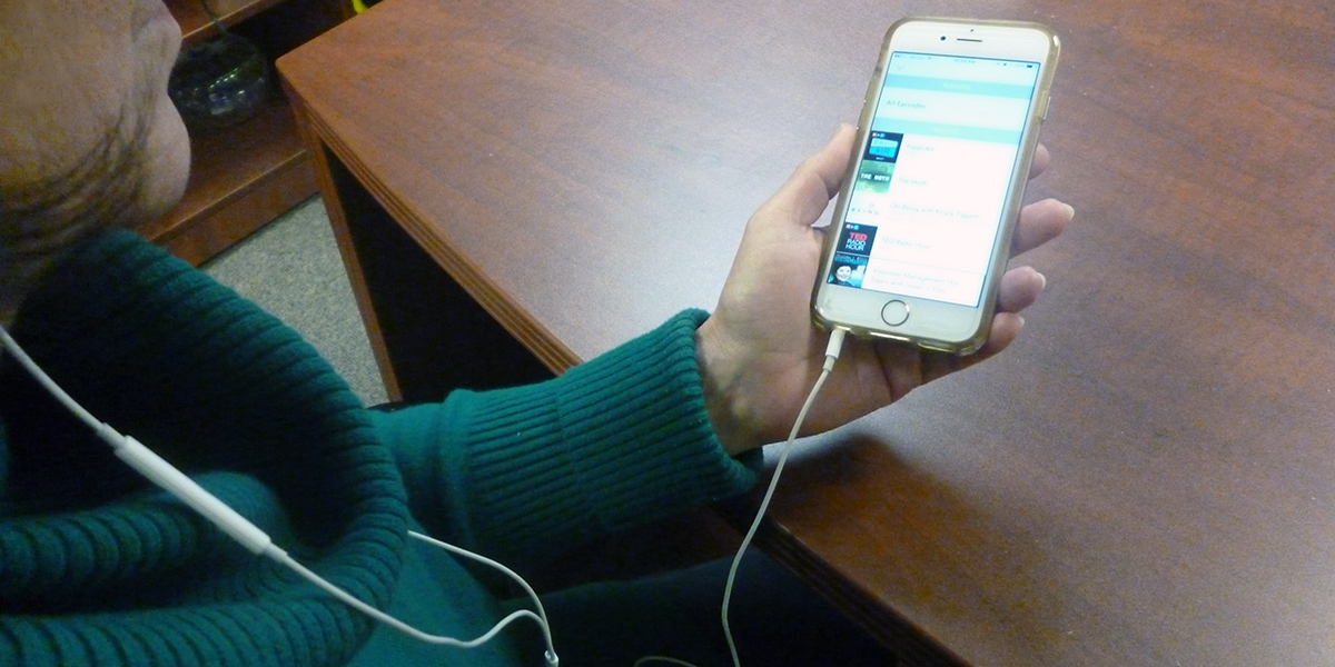 A woman listening to a podcast on her iPhone