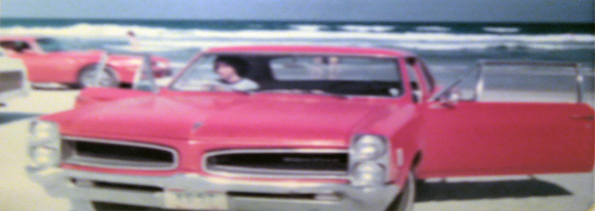 Kathy seated in her 1966 red Pontiac LeMans parked on Daytona Beach.