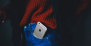 Close up of an iPhone in the front pocket of someone's jeans