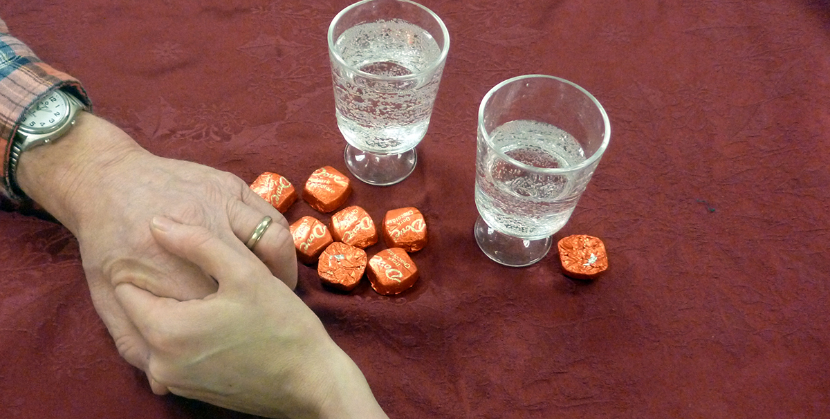 Couple holding hands on table covered in red table cloth with drinks and chocolates.
