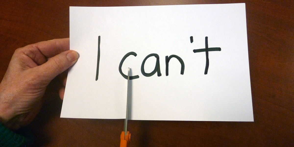 "Someone cutting through a sign that says ""I can't"" with scissors"