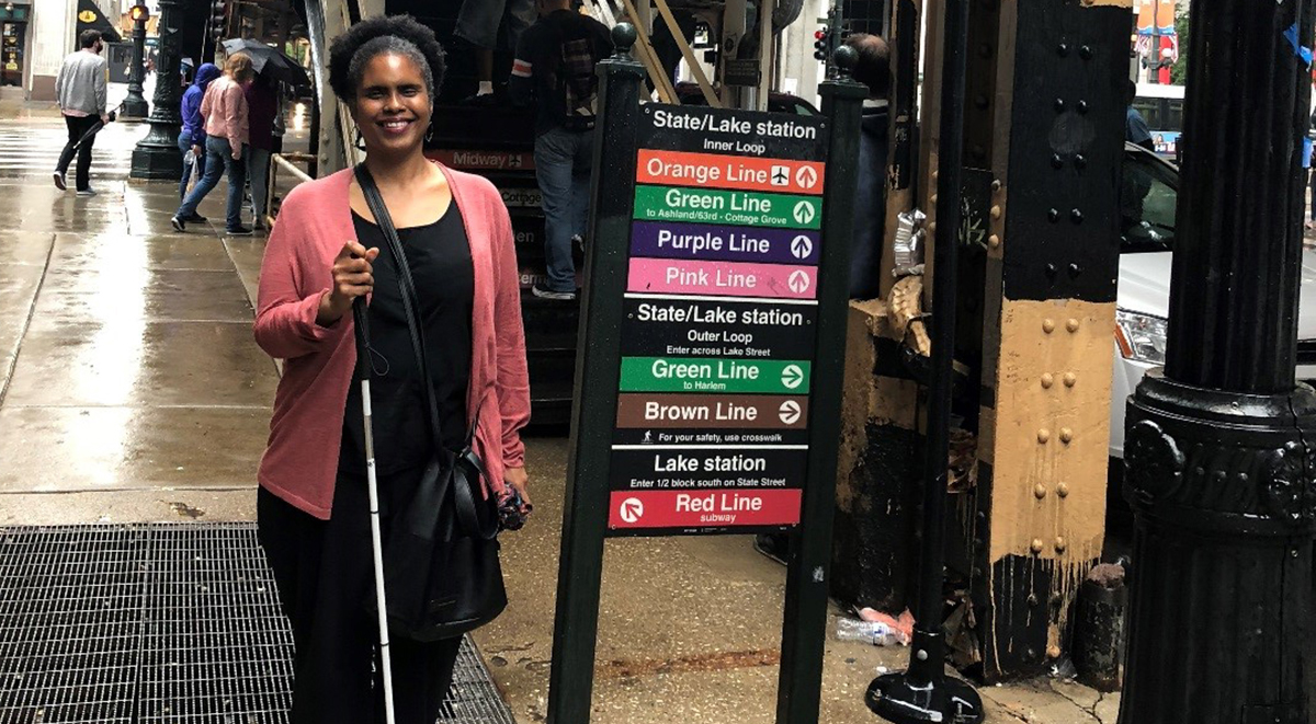 Angela standing with her cane next to the sign for the 'L' in the Loop.