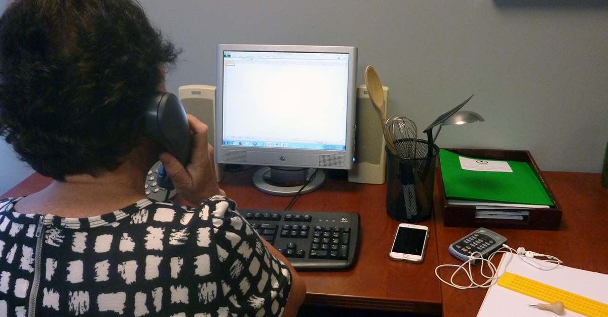 Woman at desk on the phone and using the computer. A set of tools are at hand, including her smart phone, Victor Reader Stream, braille slate and stylus and a set of cooking utensils.