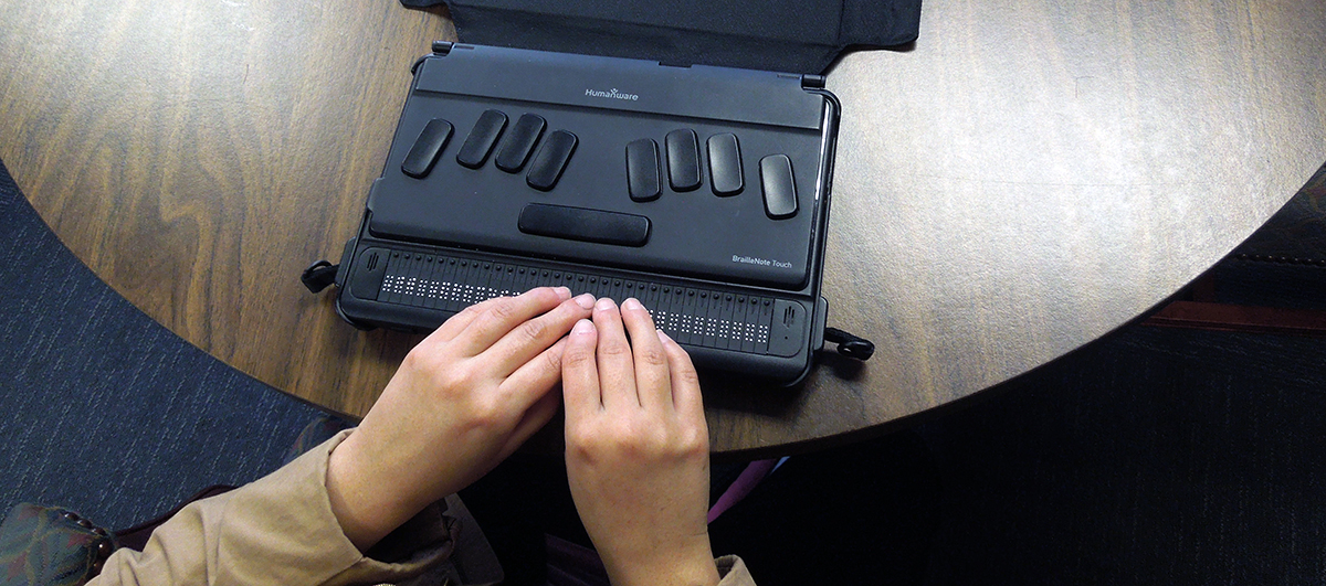 Sumaya uses reads the refreshable braille display on her BrailleNote Touch.