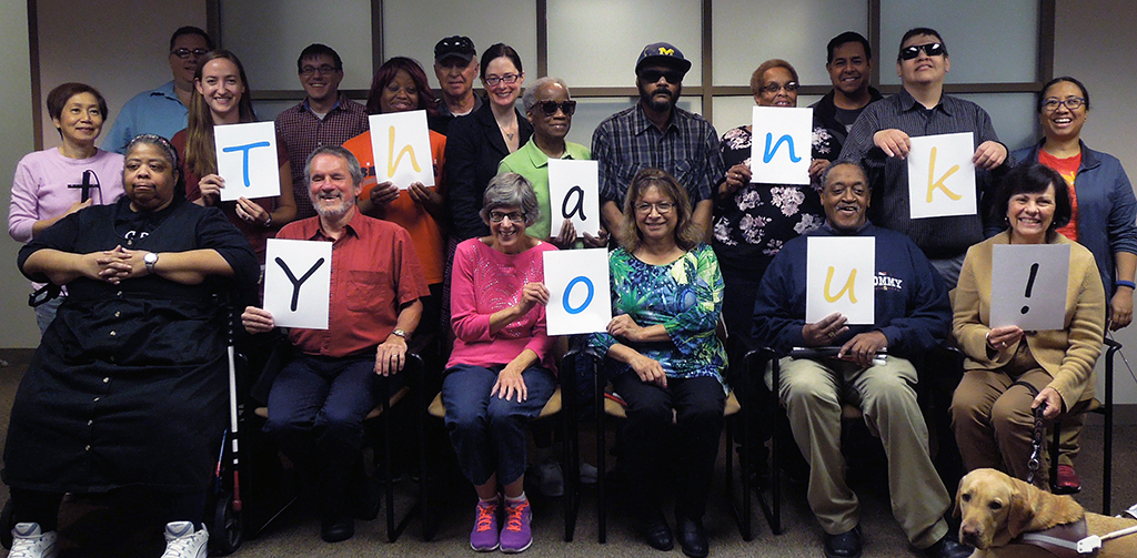 """Group of smiling clients and staff hold up cards that spell out """"Thank you!"""""""