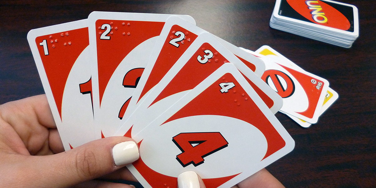 Hands holding a set of brailled Uno cards
