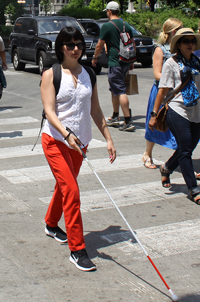 Andrea using her white cane to cross a street