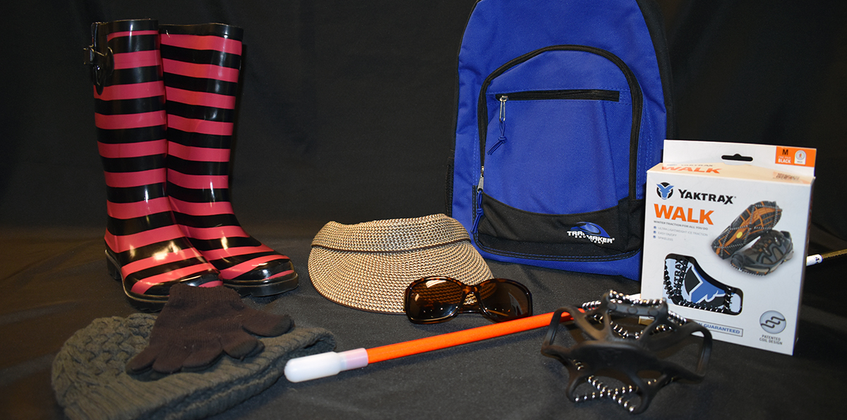 Gear for mobility in all types of weather: boots, sun visor, white cane, backpack, sun glasses and yuks