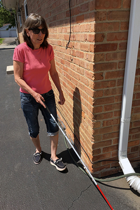 Mary Pat uses her cane to detect the back wall of her house and the beginning of the patio.