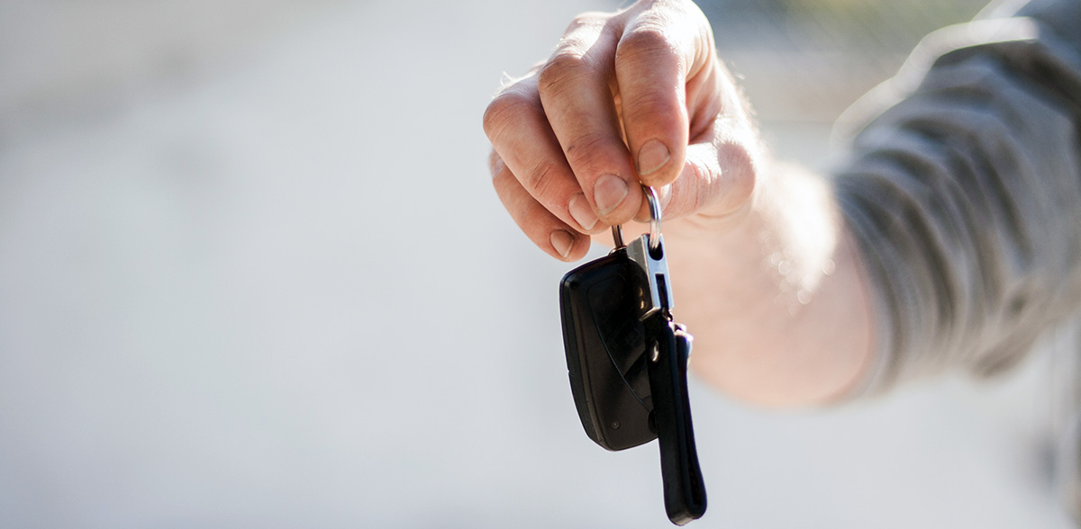 Man's hand holding out car keys
